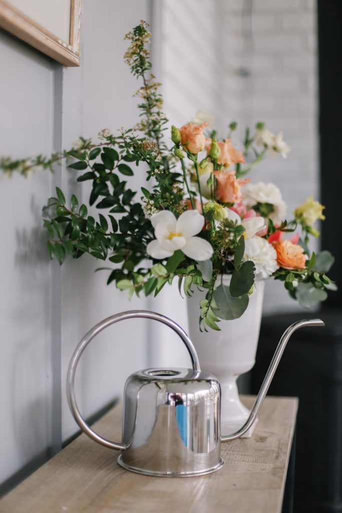 A vase of flowers on a table with a silver watering can
