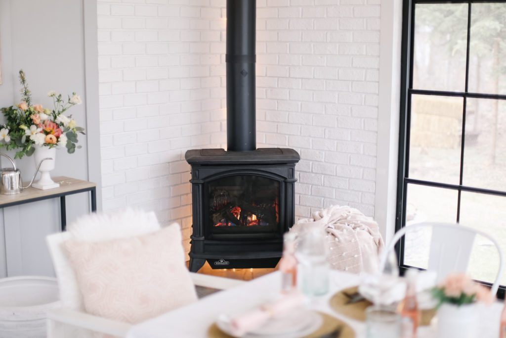 A black stove fire place sitting in front of a wall of white bricks