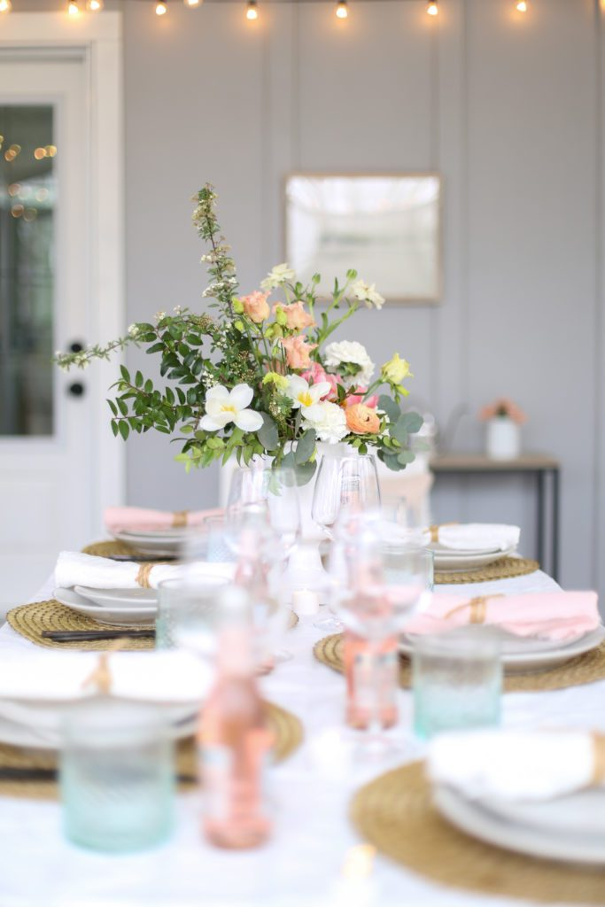A dining table set with pinks and greens