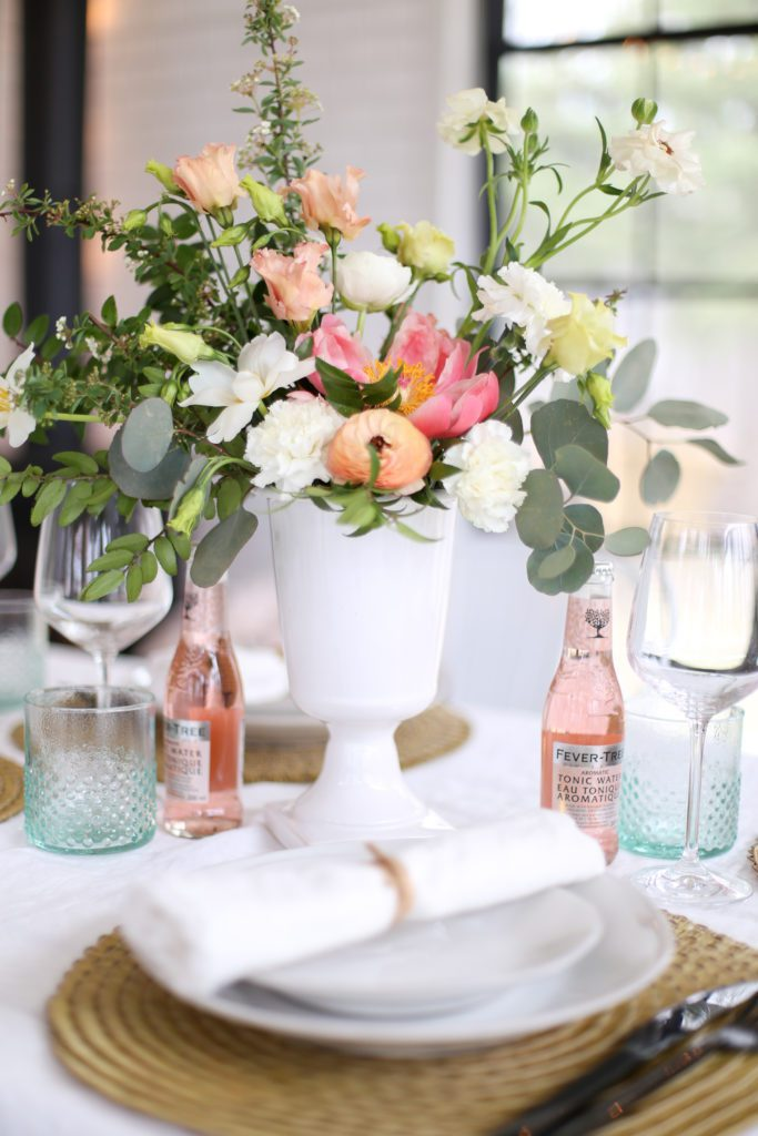 An undone floral arrangement with white, pink and peach flowers plus greens