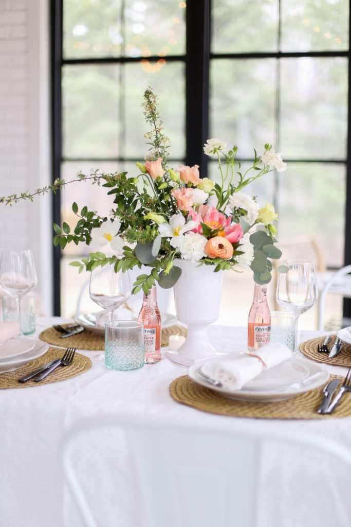 A vase of flowers on a mother\'s day tablescape next to a window