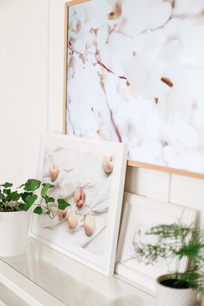 An art print of peaches displayed on a console table under a TV