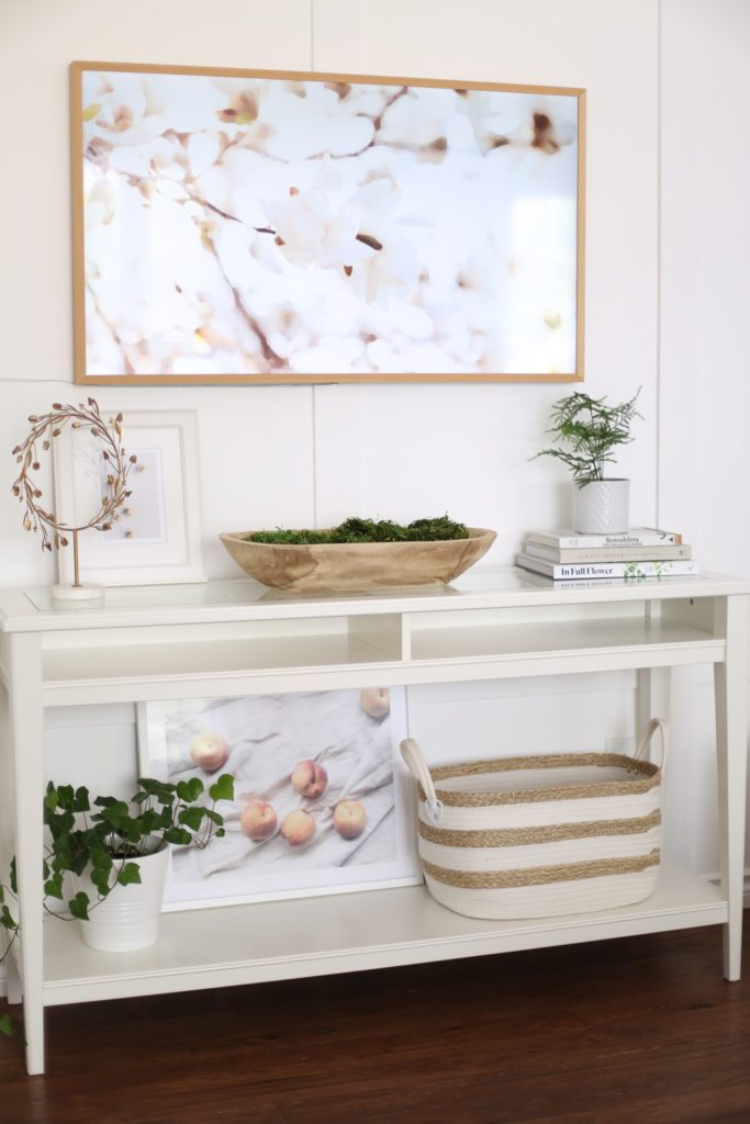 A console table with baskets, book and plants