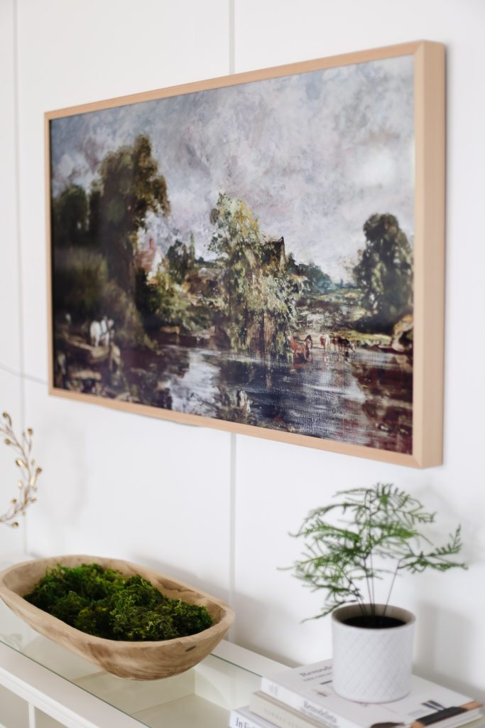 A TV with white oak frame and vintage painting displayed as digital art