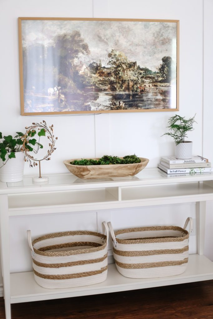 A white console table with plants, books and baskets and a Samsung Frame TV displayed above