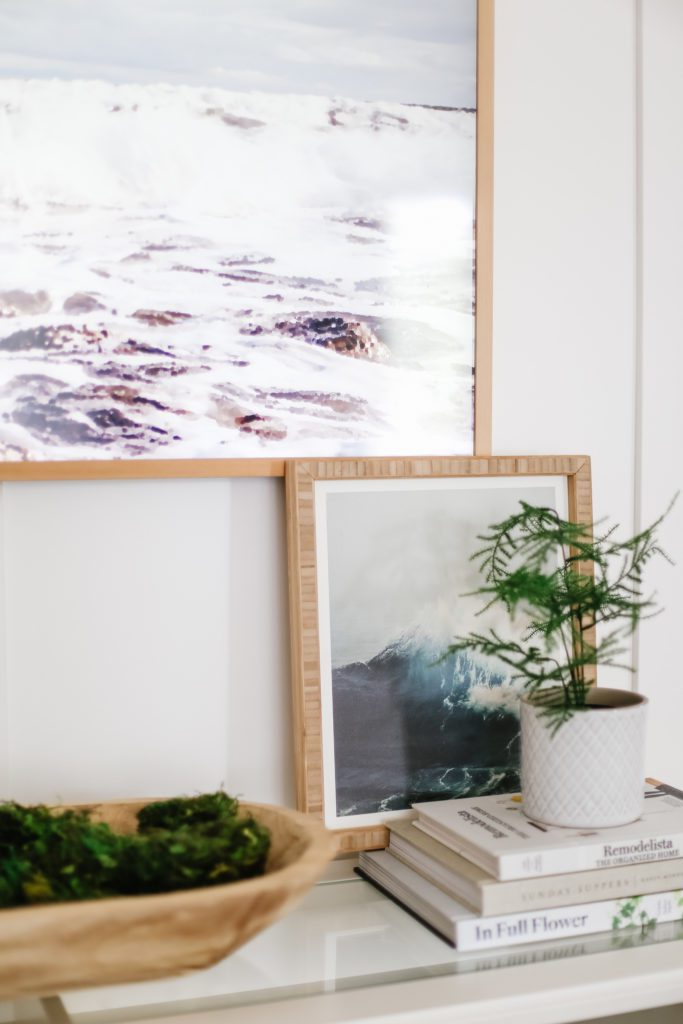 Samsung Frame TV displayed above a painting of the ocean and potted plant sitting on some books