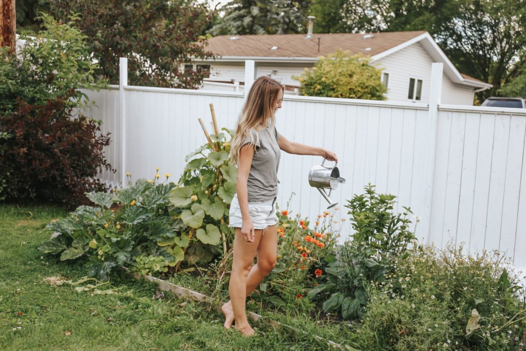 A woman watering plants standing in front of a white fence.