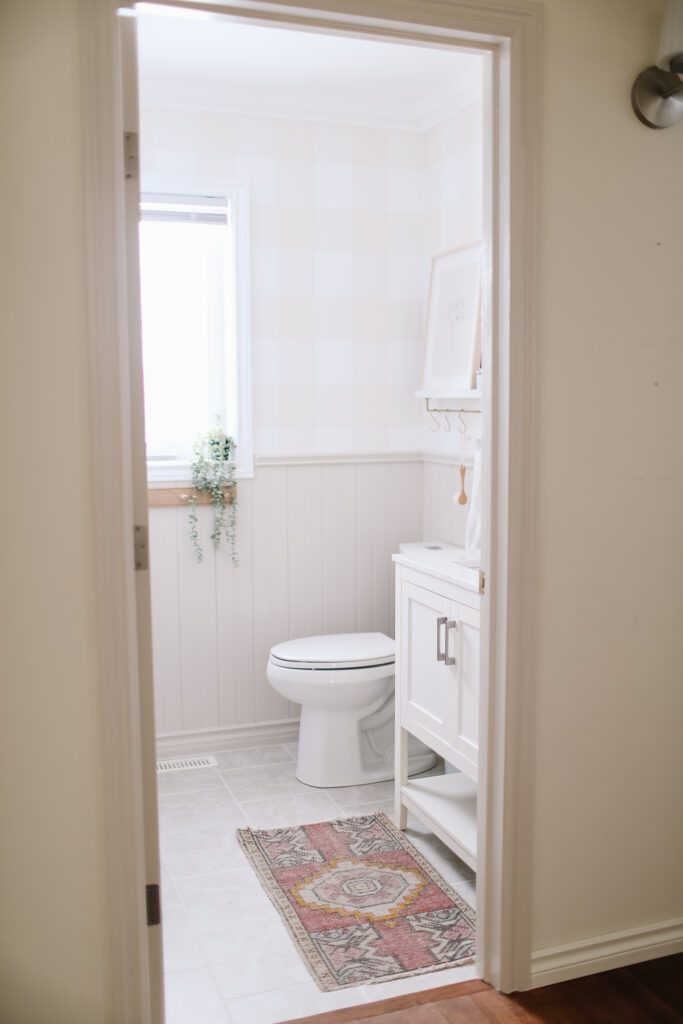 pink vintage rug in front of a bathroom console