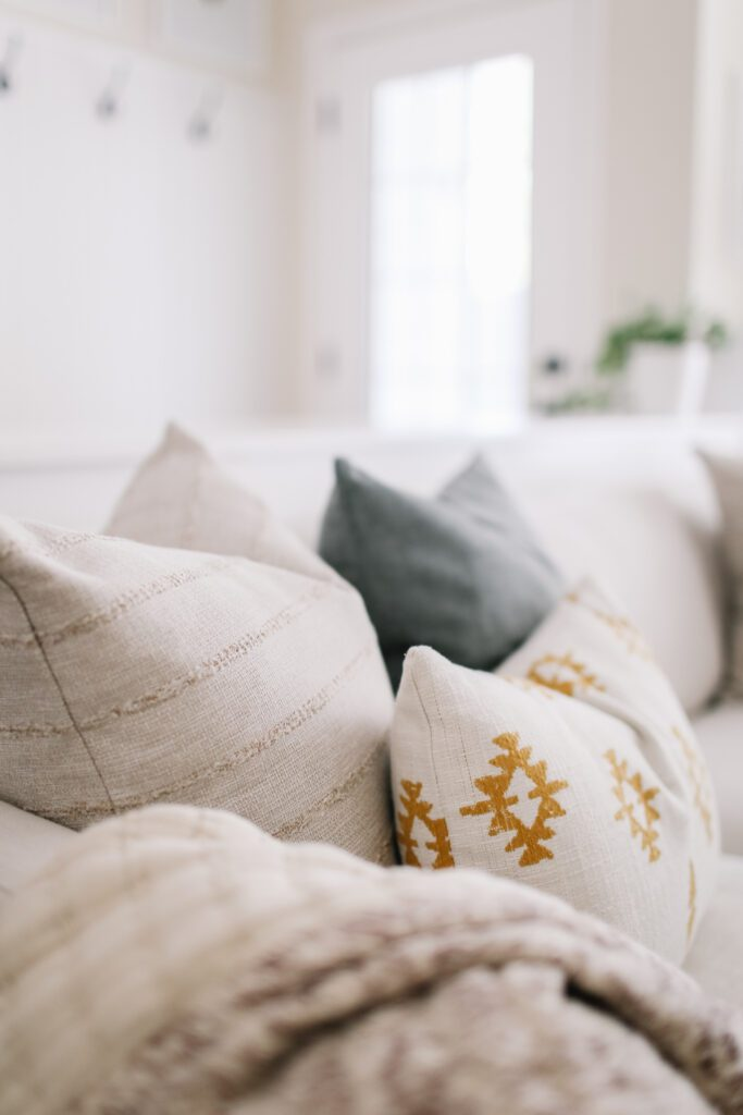 yellow, blue and neutral throw pillows on a couch