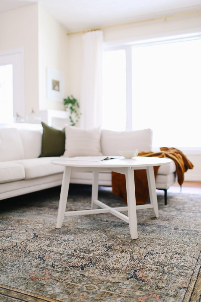 Living room with a sectional, round white coffee table and vintage rug