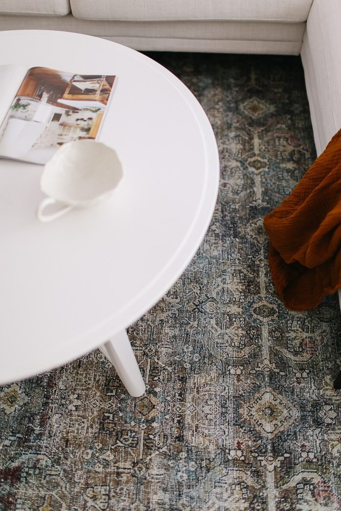 close up of a vintage style rug underneath a white coffee table