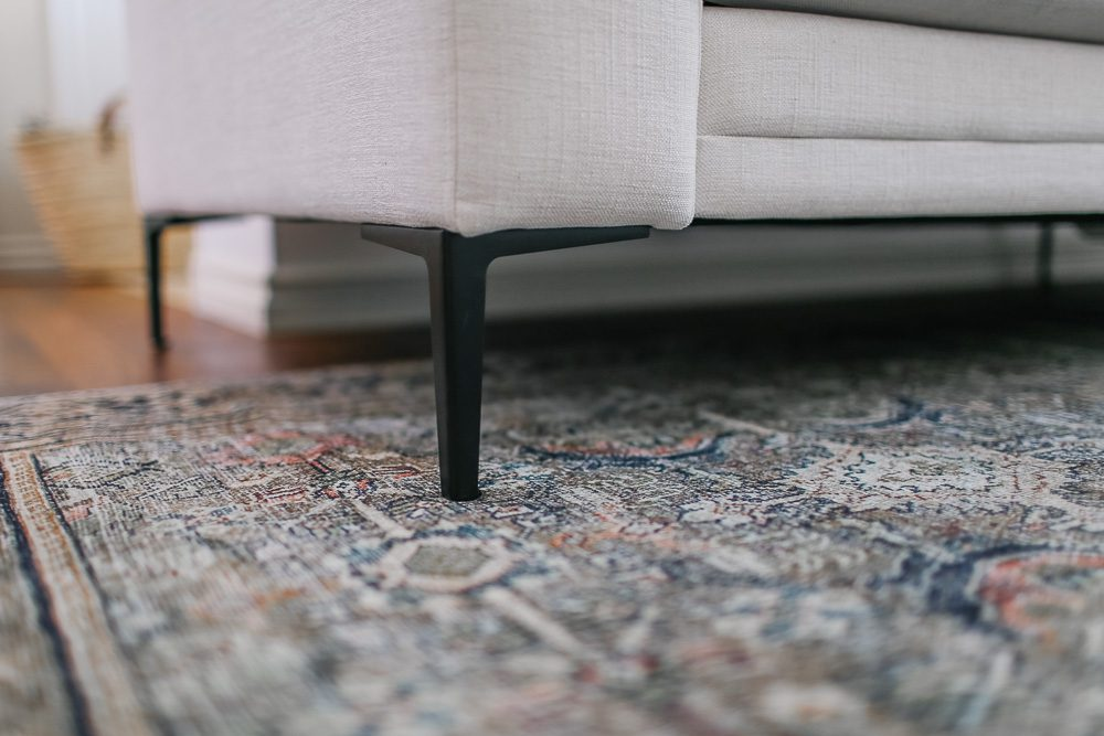 Foot of sectional sofa sitting on a vintage rug